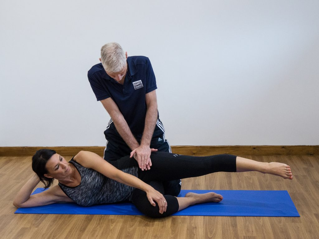 Ober test position with therapist stabilizing pelvis